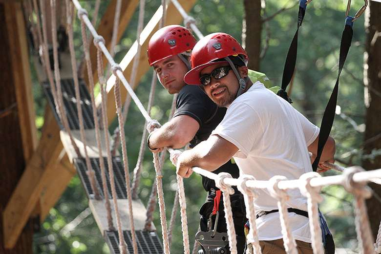 two men on a suspended bridge in the woods