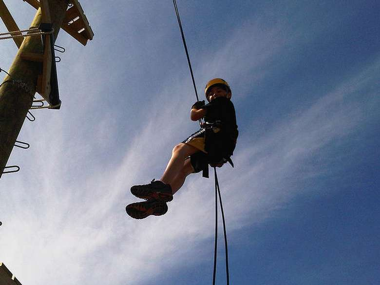a boy descending on a rope