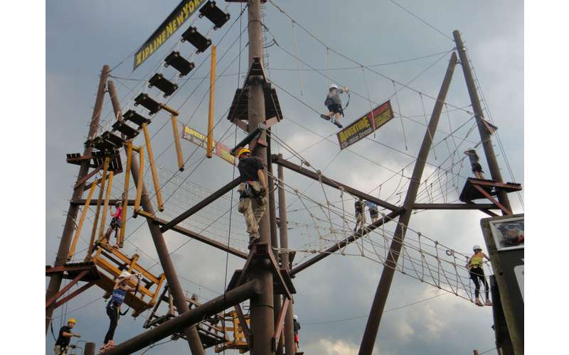 people traversing a large ropes course adventure tower