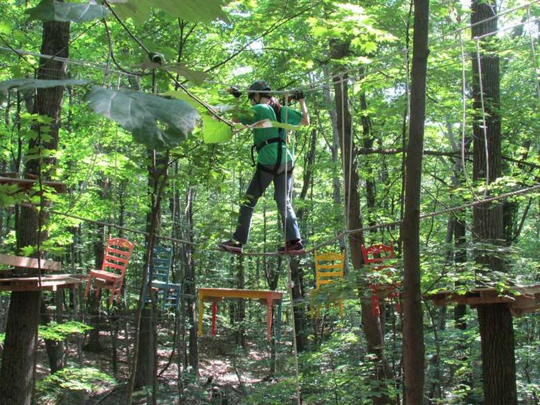 teen traveling across an aerial ropes course among the trees