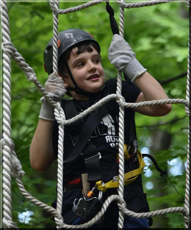 a boy holding onto a rope net
