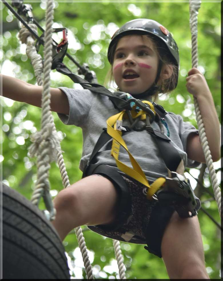 a girl traversing an aerial ropes course