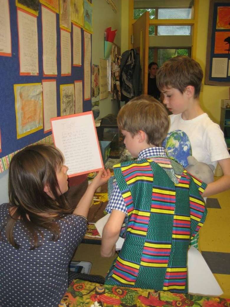 female teacher showing two boys an educational paper