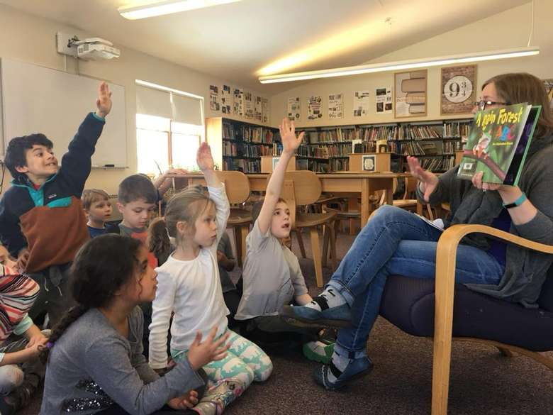kids raising hands during a classroom reading