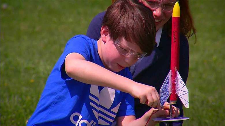 boy preparing to launch a red rocket