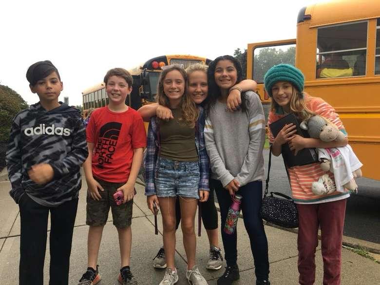 group of kids outside school buses
