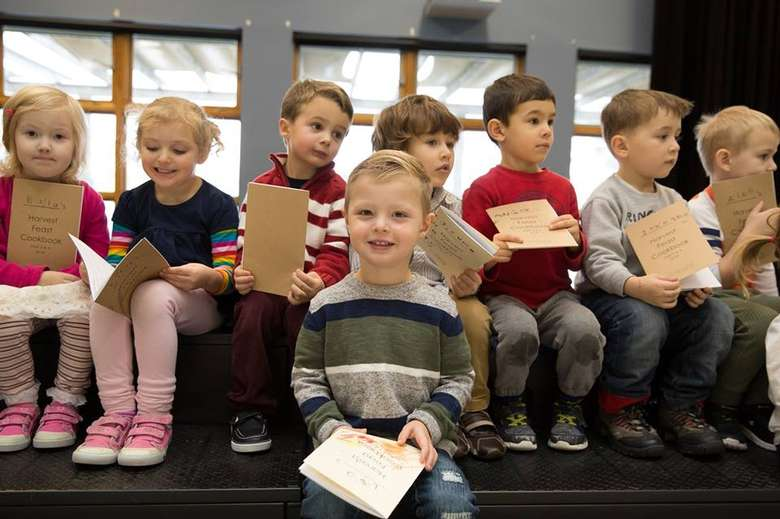 group of young kids with small booklets