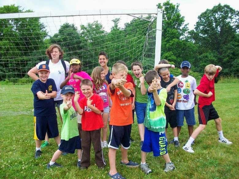kids posing in front of soccer goal net