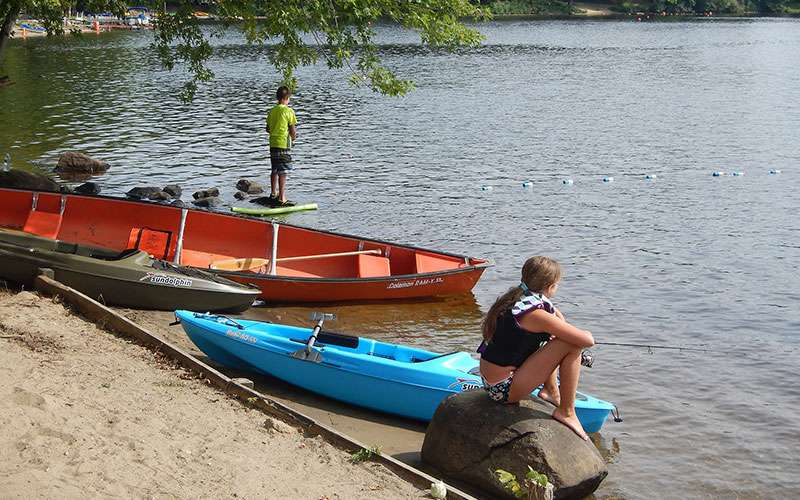 kids near two kayaks and a canoe