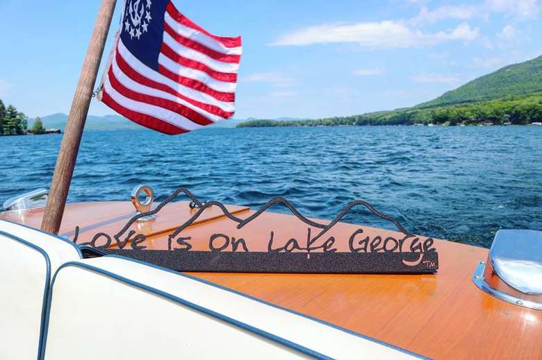 Love is on Lake George text on black metal sign with the cutout of the mountains sitting on the stern of a wooden boat.