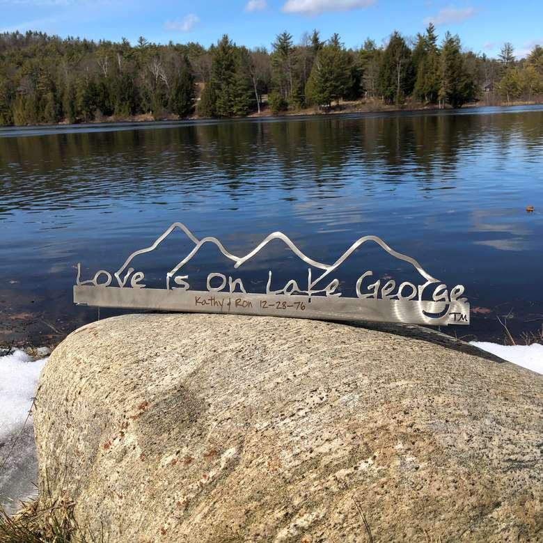 Love is on Lake George on a stainless steel metal sign with the cutout of the Mountains.