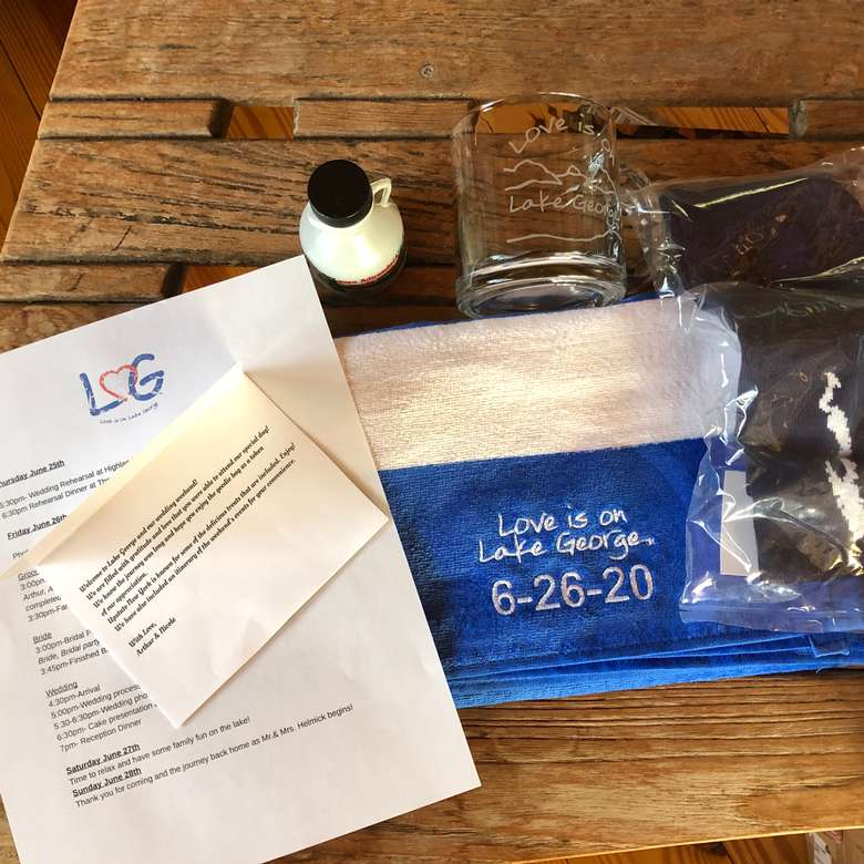 Custom Wedding Welcome bag that includes a note, a small jug of maple syrup, a Love is on Lake George blue/white cabana style velour beach towel and a Love is on Lake George clear coffee mug