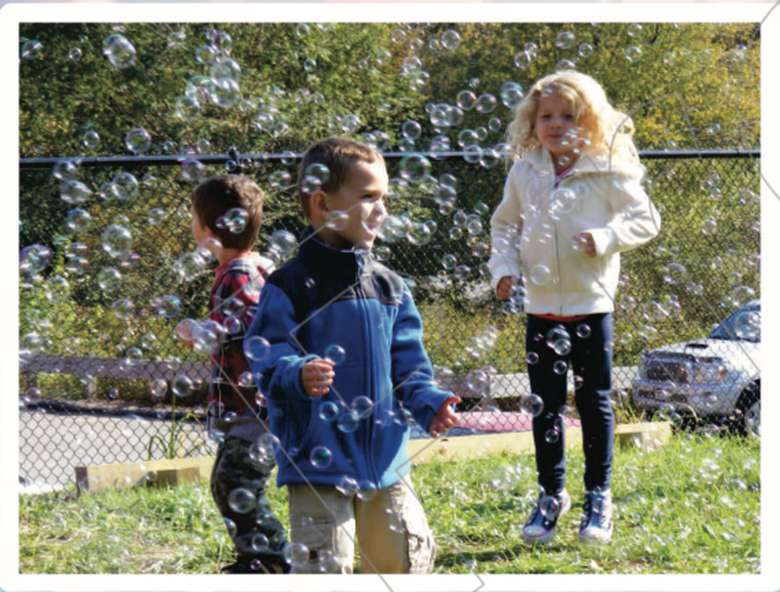 three kids outdoors at a bubble party
