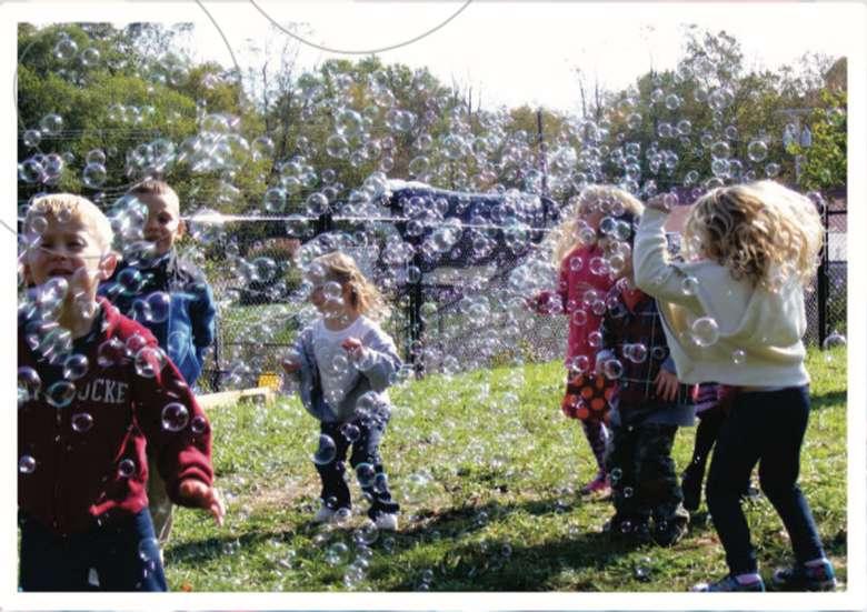 kids surrounded by tons of bubbles in the air