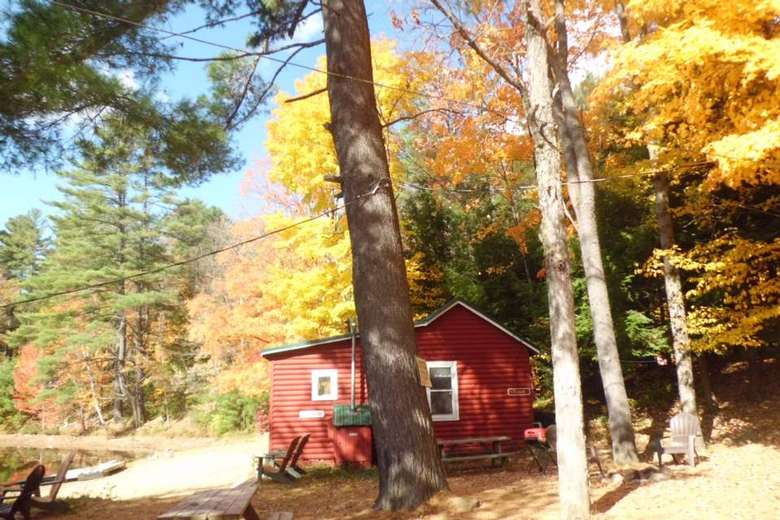 red cottage near trees with bright yellow foliage