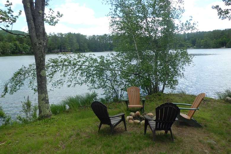four adirondack chairs near a fire pit by the lake