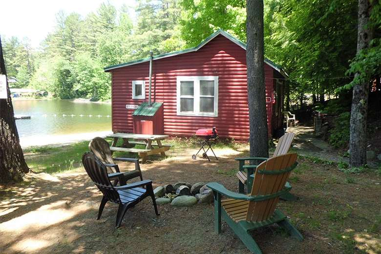 red cottage near a picnic table and shoreline