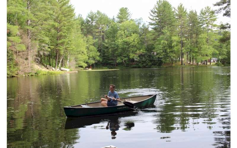 person canoeing on a lake