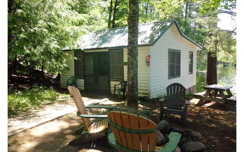 white cottage near picnic table and chairs