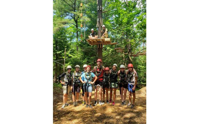 group of people at treetop adventure course