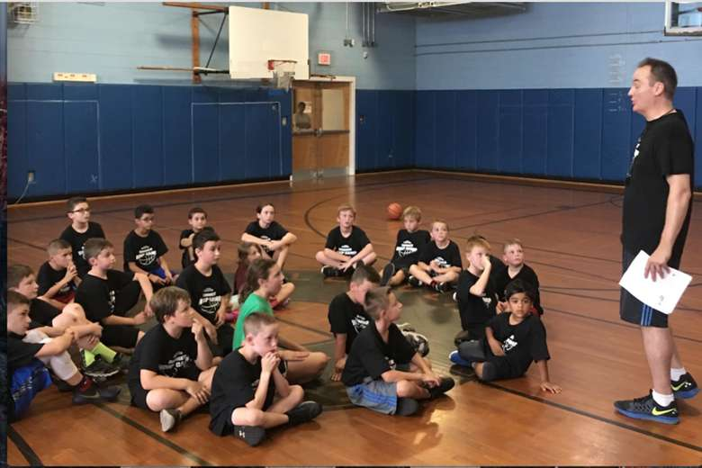 kids sitting and listening to an instructor on a basketball court