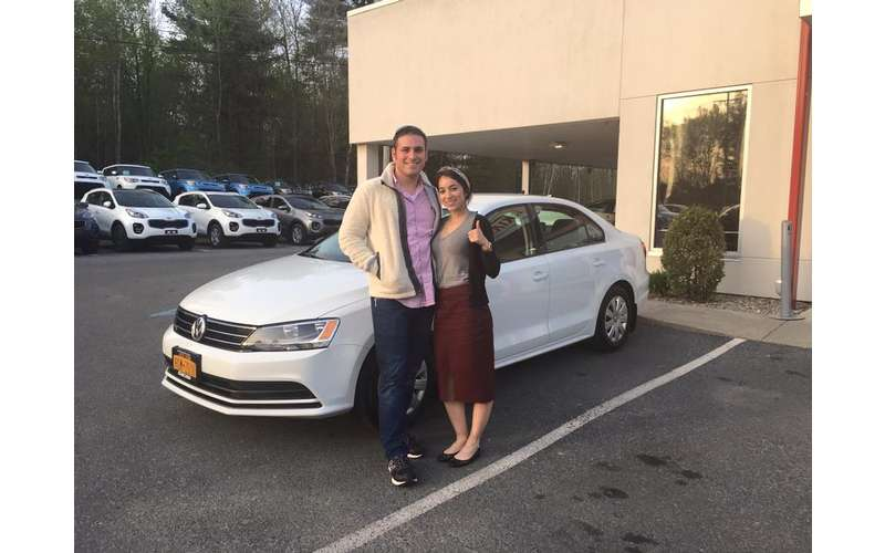 man and woman standing near a white car