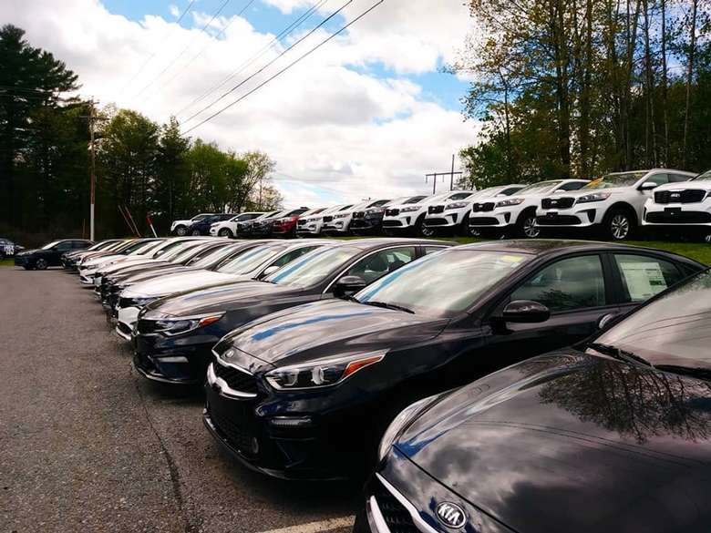 two rows of parked cars at a dealer