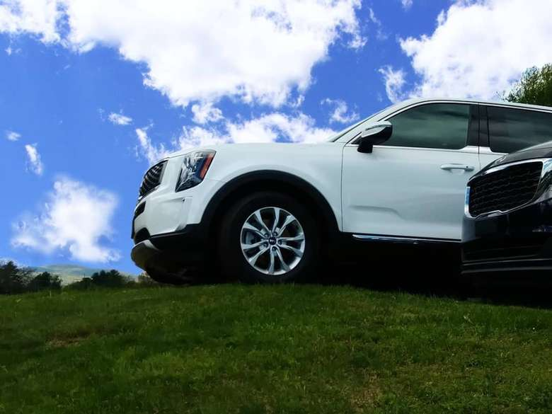 white vehicle and a black vehicle on a grassy hill