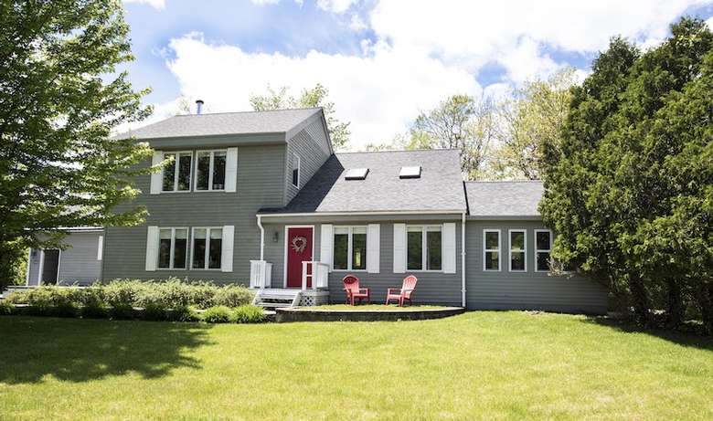 large house with red doors and grassy lawn