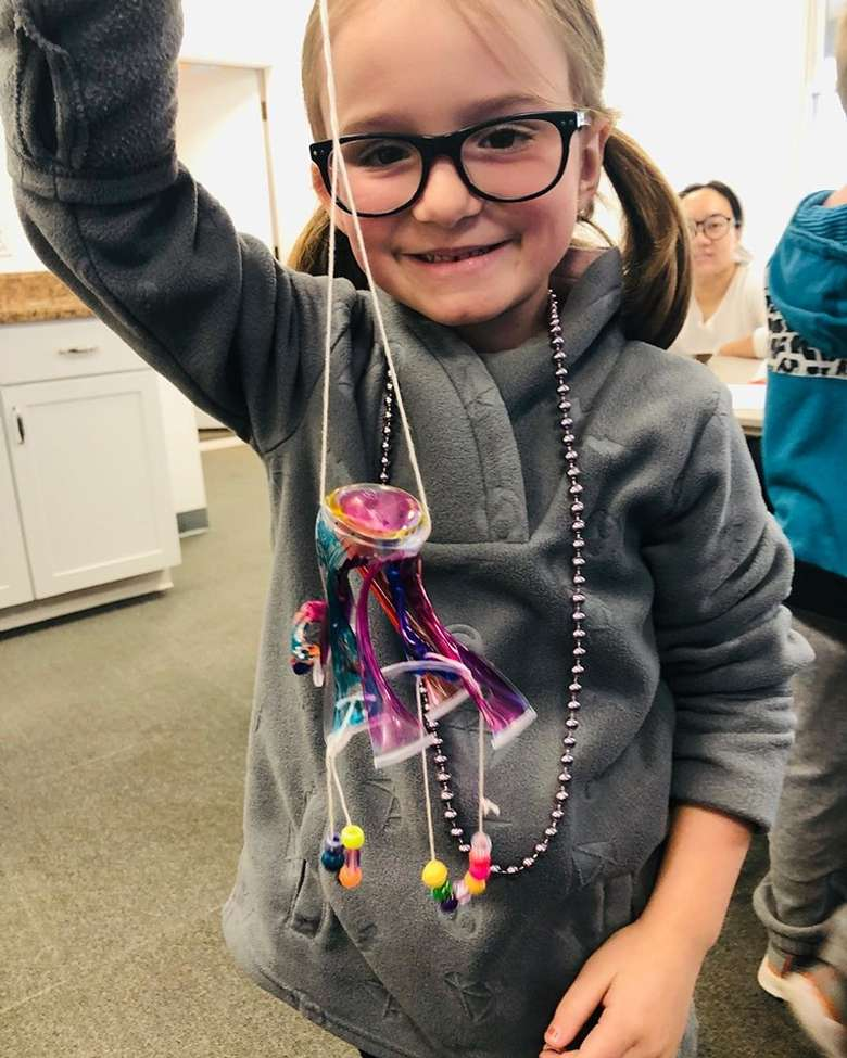girl holding up handmade necklace
