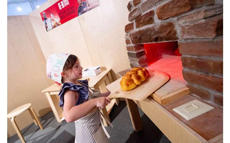girl putting pretend bread in pretend oven