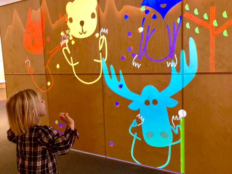 kid in front of interactive digital wall