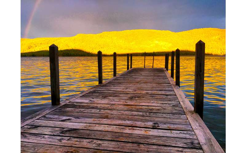 wooden dock and yellow sunset shining on mountains