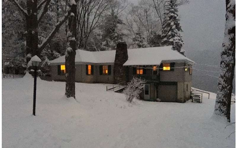 a cottage surrounded and covered by snow