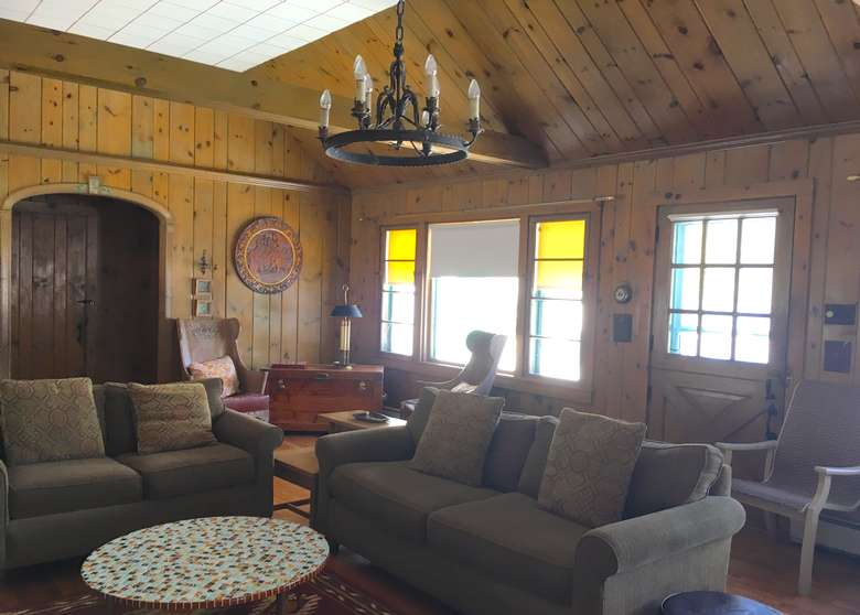 couches in a living room with wooden walls