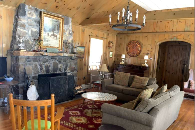 rustic living room with a large stone fireplace