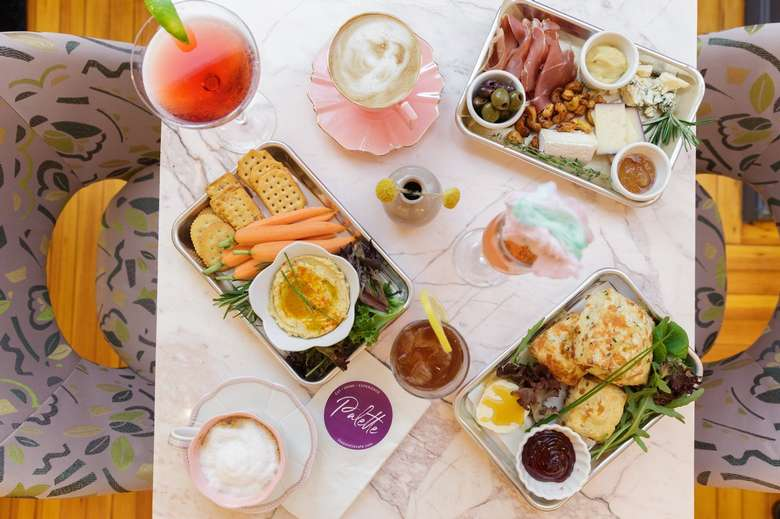 various dishes, drinks, and a palette cafe menu on a table