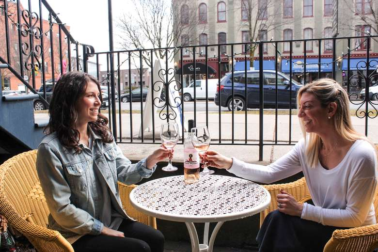 two women with wine at a table outdoors