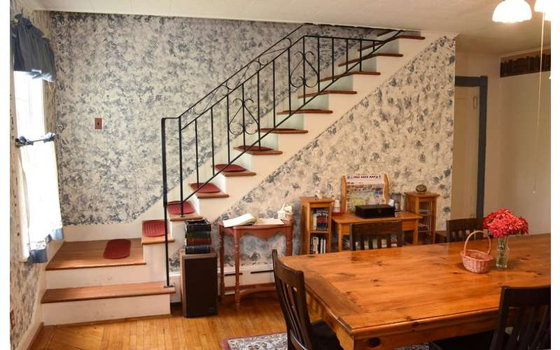 wooden dining table near stairs