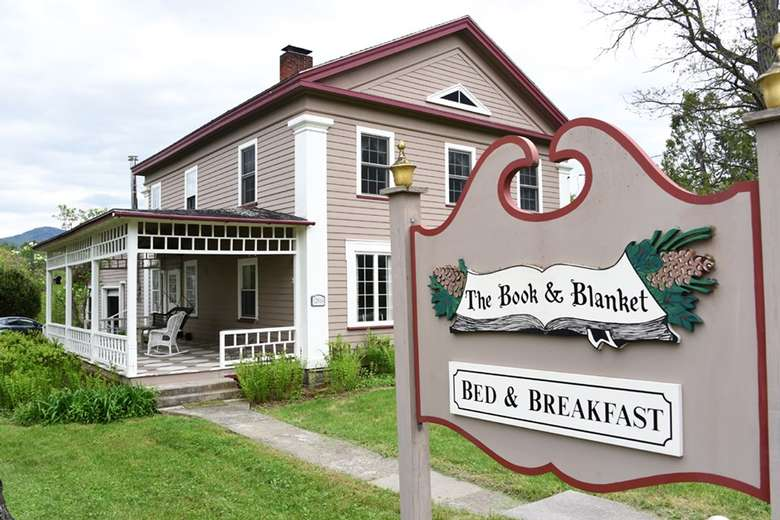 book and blanket bed and breakfast sign near a house