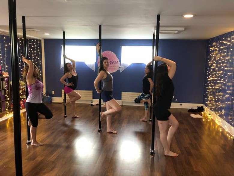 five women practicing pole dancing