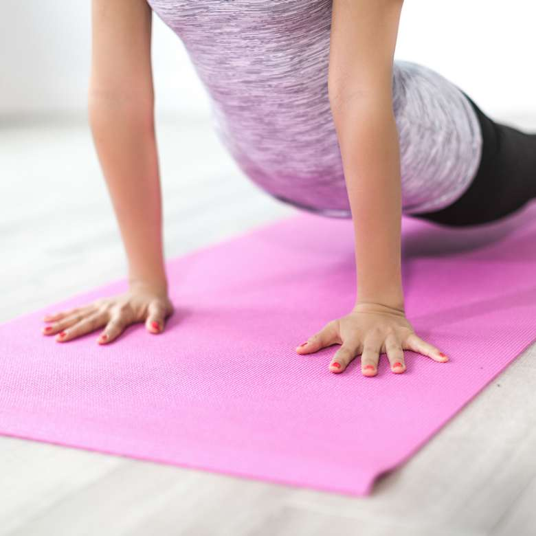 woman performing yoga pose on a mat