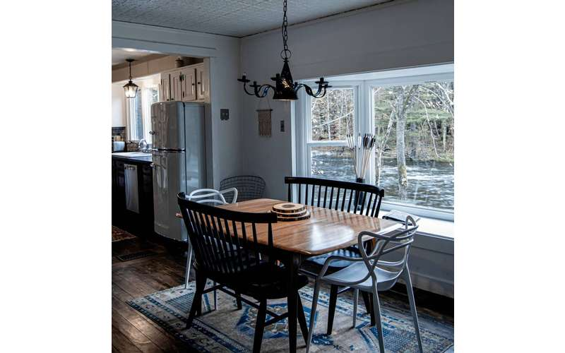 dining room with table and window view of a river warner's camp adirondack cabin rental