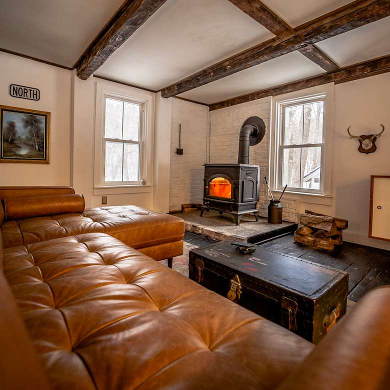 living room with brown sofa and wood burning stove warners camp cabin rental