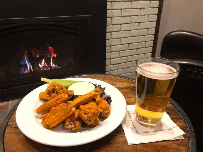 a table by a fireplace with a plate of buffalo wings and a glass of beer on top