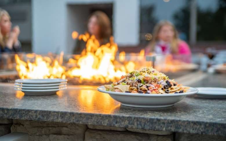 plates of food on a patio table fire pit