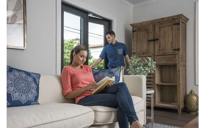 man closing door while woman is sitting on couch with a book
