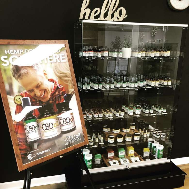 sign near a glass case with shelves of cbd products