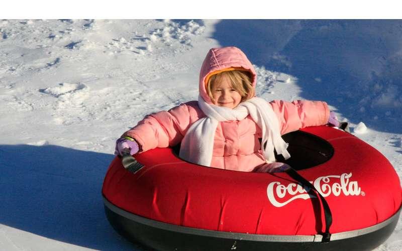 little girl in red snow tube