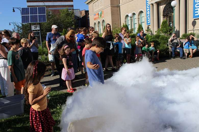 group of people outdoors with a smoke filled science experiment
